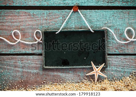 Blank slate for your seafood menu or advertisement hanging on grungy weathered blue wooden boards with sea sand and a starfish in a pretty marine background - stock photo