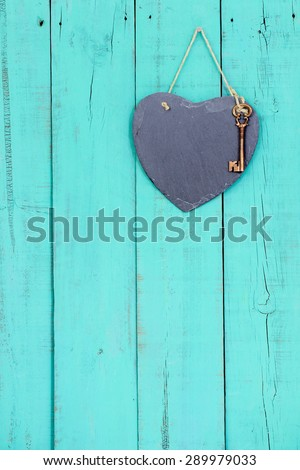 Blank slate heart with bronze skeleton key hanging from rope on rustic antique teal blue wooden background - stock photo