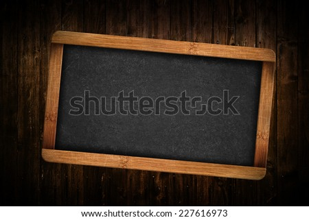 Blank Slate on Brown wood planks as background. - stock photo
