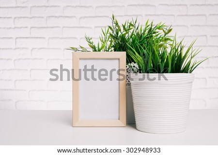 Blank small wooden photo frame and house plants - stock photo
