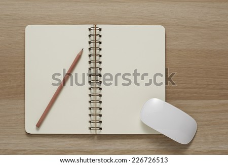 Blank Spiral Note Pad, computer mouse and Pencil on Wood Background. - stock photo