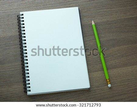 blank spiral notebook and pencil on dark wood background - stock photo