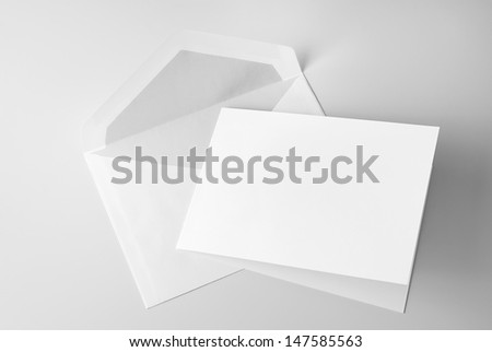 Blank stationery: card and envelope over grey background with shadow - stock photo