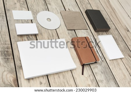 Blank stationery set on old wood background: business cards, plastic card, booklet, notebook, notepad, CD, box and pen. Vintage style - stock photo
