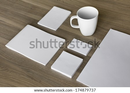Blank stationery set on wood background / a4 paper, business cards, letterheads, booklet, notepad and cup - stock photo