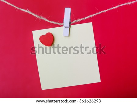 Blank sticky note with red heart hanging against red background. - stock photo