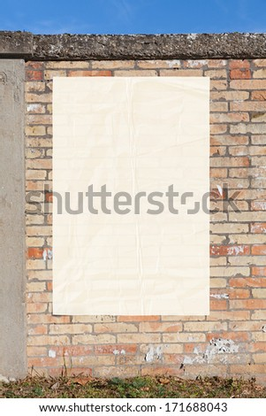 blank street advertising billboard glued on brick wall - empty white poster,sheet of paper, copy space    - stock photo