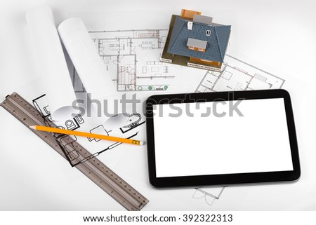 blank tablet and house scale model on architectural blueprints - stock photo