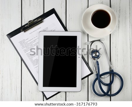 Blank tablet, clipboard, stethoscope and cup of coffee on wooden background - stock photo