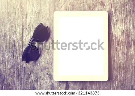 Blank tablet with sunglasses on a wooden table - stock photo