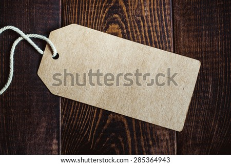 Blank tag on dark wood background - stock photo