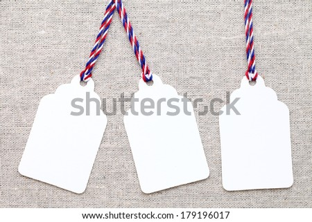 blank tag or label with colorful string on burlap background - stock photo