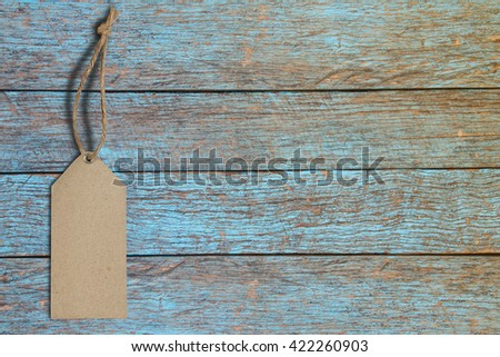 Blank tag tied. Price tag, gift tag, sale tag, address label on old blue wooden  - stock photo