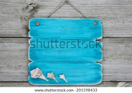 Blank teal blue sign with seashells hanging on rustic wooden background - stock photo