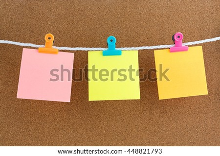 Blank three page of color paper with Letter Clips on cork bulletin board - stock photo
