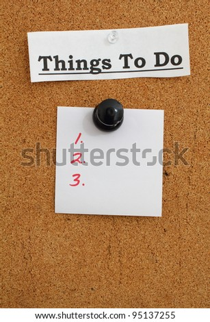 Blank to do list note pinned to a cork bulletin board with a giant push pin. - stock photo