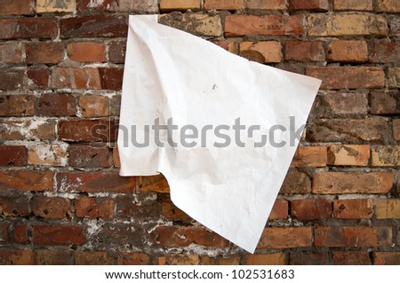 Blank torn paper poster on an old brick wall - stock photo