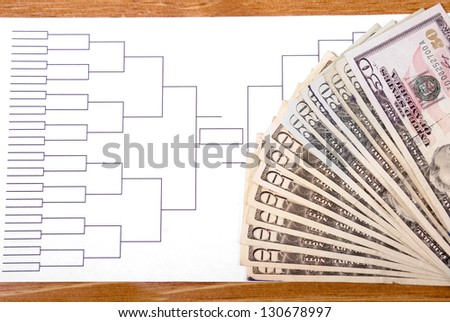 Blank tournament bracket with fanned money representing gambling - stock photo