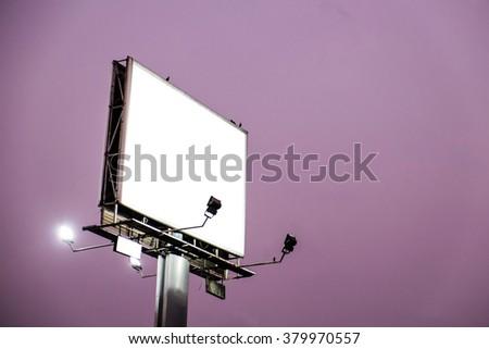 Blank white billboard on evening sky - stock photo