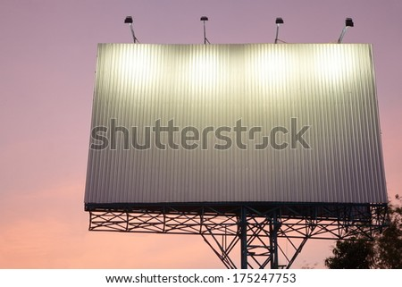 blank white billboard on the edge of country road sunset sky with spot light.  - stock photo
