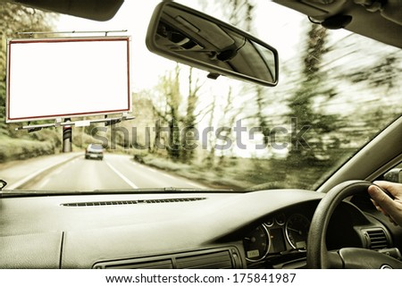 Blank white billboard with space for your advertisement seen from the inside of a car - stock photo