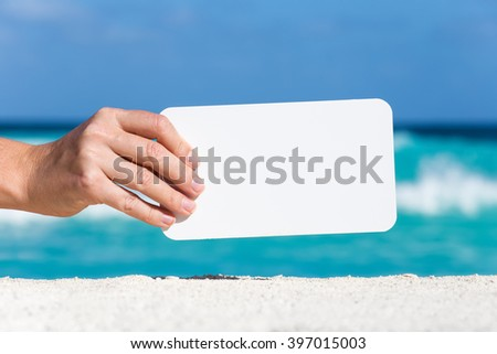 Blank white board in female hand on sand against turquoise caribbean sea water. Tropical summer vacation concept - stock photo