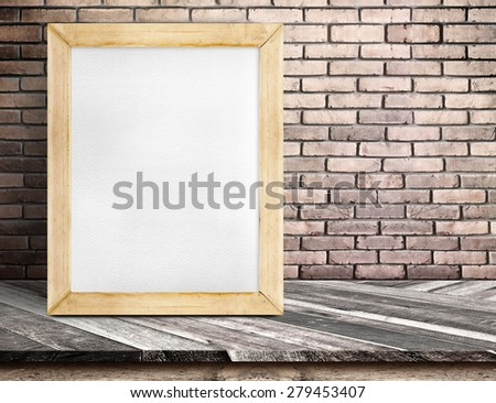 Blank white board wood frame on diagonal wooden table at red brick wall, Template mock up for adding your design and text. - stock photo