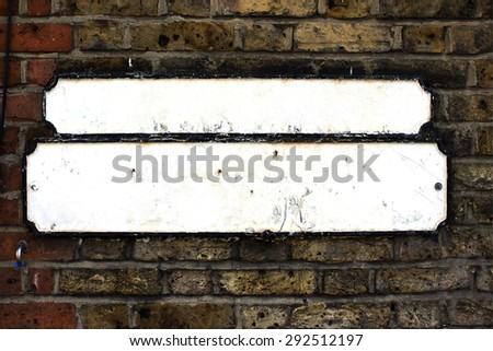 Blank white British street sign on brick wall - stock photo