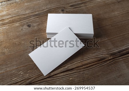 Blank white business cards on a dark wooden background. Mockup for branding identity. Template for graphic designers portfolios. Top view. Shallow depth of field.  - stock photo