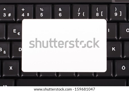 Blank, white card on black computer keyboard buttons, top view. - stock photo