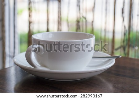 Blank white cup with a teaspoon on the table in a cafe. Cup with tea or coffee drunk, empty - stock photo