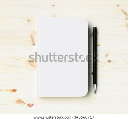 Blank white diary cover with pen on wooden table, mock up - stock photo