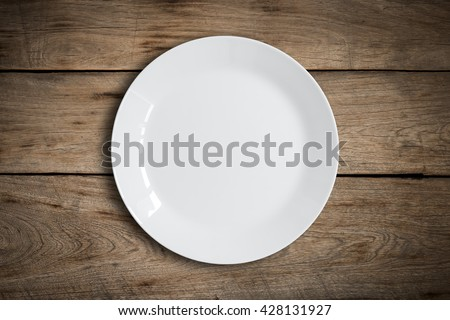 Blank white dish on a wood background. - stock photo