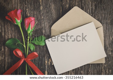 Blank white greeting card with brown envelope and red rose flowers with ribbon bow on wooden table with vintage and vignette tone - Valentine and love concept - stock photo