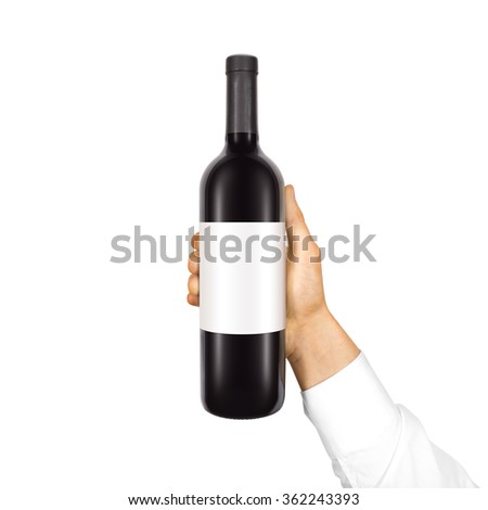 Blank white label mock up on black bottle of red wine in hand isolated. Alcohol bottle mockup presentation ready for logo design. Full drink bottle template with empty sticker. Clear tag vine bottle. - stock photo