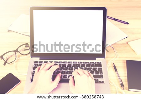 Blank white laptop screen with girl hands and office accessories on wooden table, mock up  - stock photo