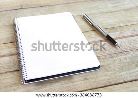 Blank white notebook with pen on wood desk. shallow depth of field - stock photo