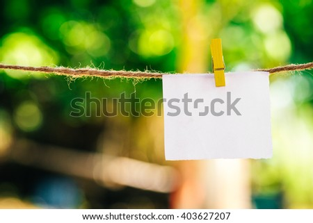 Blank white paper and clippaper  hanging on the clothesline with bokeh nature background.Designer concept. - stock photo
