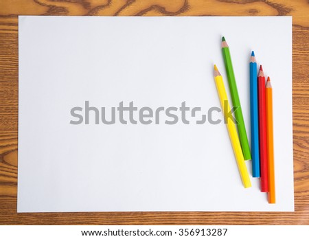 Blank white paper and color pencil on wooden table - stock photo
