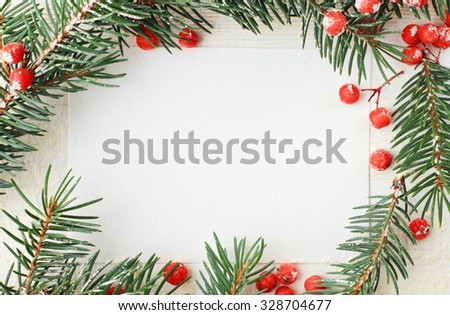 Blank white paper card framed with natural fir tree branches decor and bright red berries, wintry New Year congratulation message.  - stock photo