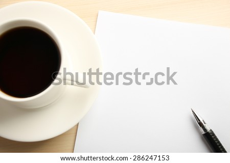 Blank white paper is on the table with ball pen and coffee aside. - stock photo