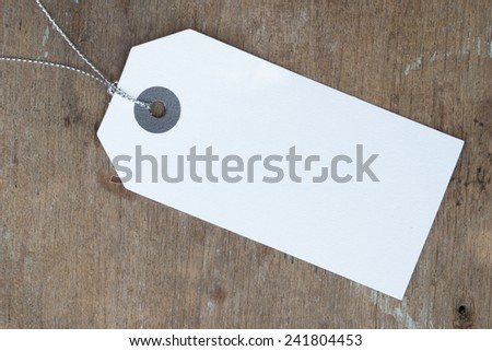 Blank white paper tag on wood surface - stock photo