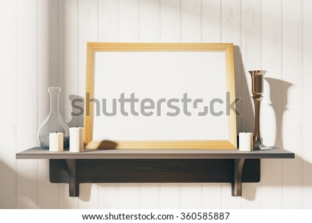 Blank white picture frame with candlesticks on brown wooden shelf, mock up - stock photo