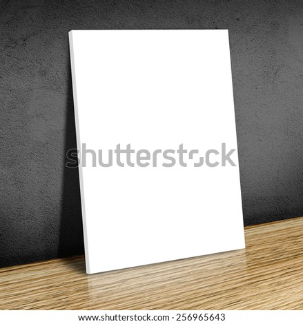 Blank white poster frame at wooden floor and black concrete wall, Canvas frame template Business concept - stock photo
