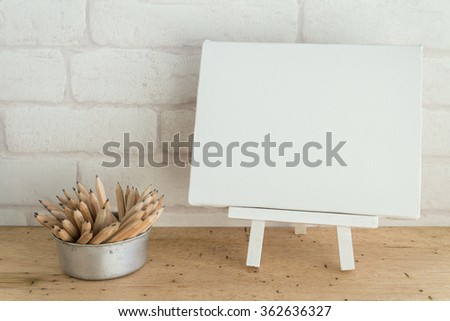 Blank white wooden easel  blank canvas and pencils on wooden table with white wallpaper background for your text - stock photo