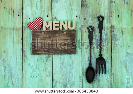 Blank wood sign with red and white heart and the word MENU hanging on antique rustic mint green wooden background by black cast iron spoon and fork; family and love concept - stock photo