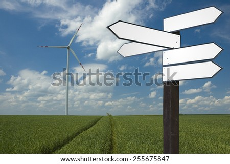 Blank wooden guidepost on a farm with wind propelled turbine generating electricity in the background - stock photo