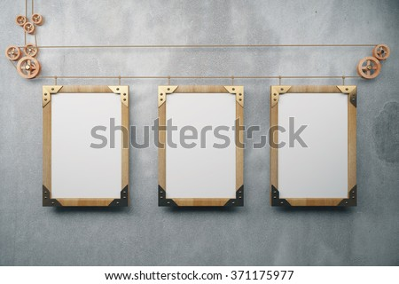Blank wooden steampunk picture frames on grey concrete wall, mock up - stock photo