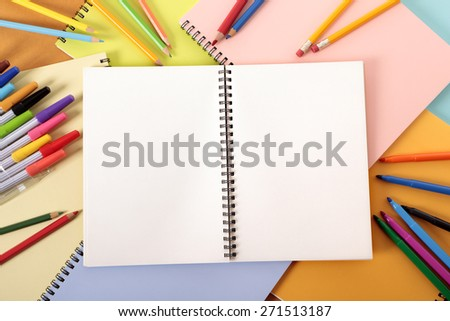 Blank writing sketch book, pencils, crayons, top view - stock photo