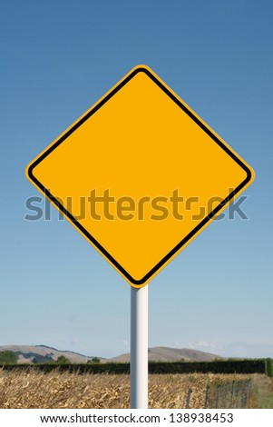 Blank yellow diamond road sign in a rural setting for  use with your own text - stock photo